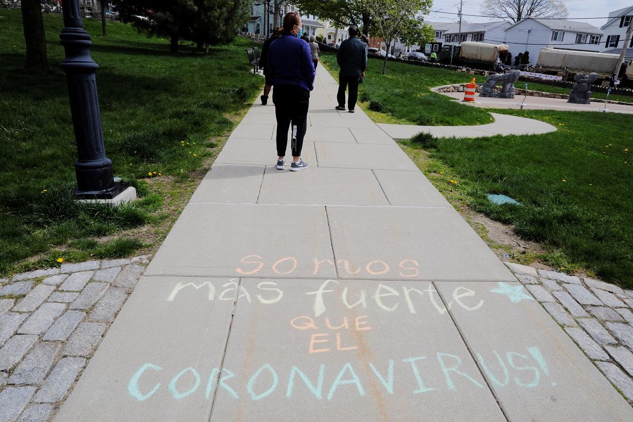 """La frase """"Somos Mas Fuerte Que El Coronavirus"""" pintada en una acera de la localidad estadounidense de Chelsea (Massachusetts). REUTERS/Brian Snyder"""