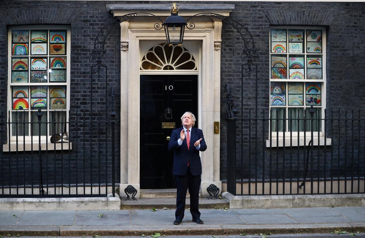El primer ministro británico, Boris Johnson, aplaude frente al número 10 de Downing Street, en apoyo a los sanitarios, durante la pandemia del coronavirus. REUTERS/Hannah Mckay