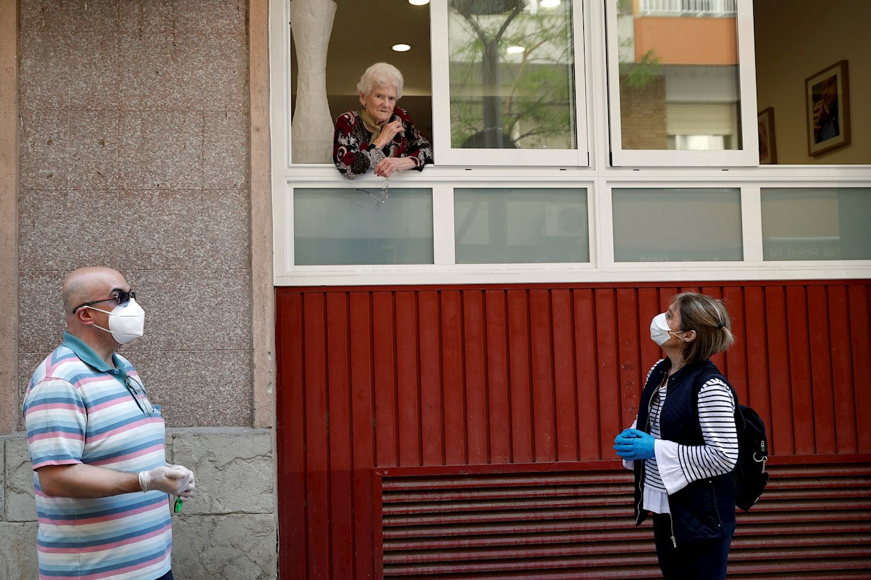 Una anciana, usuaria de una residencia geriática de L'Hospitalet de Llobregat (Barcelona), habla desde una ventana con una hija y un amigo de la familia. EFE/Toni Albir
