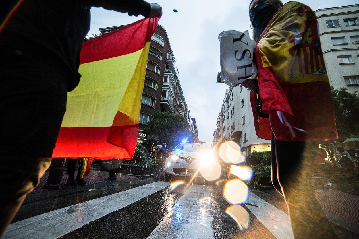 Varias personas delante de una patrulla de Policía Municipal, durante la concentración de vecinos del barrio madrileño de Salamanca contra la gestión del Gobierno en la pandemia del coronavirus. E.P/Joaquin Corchero