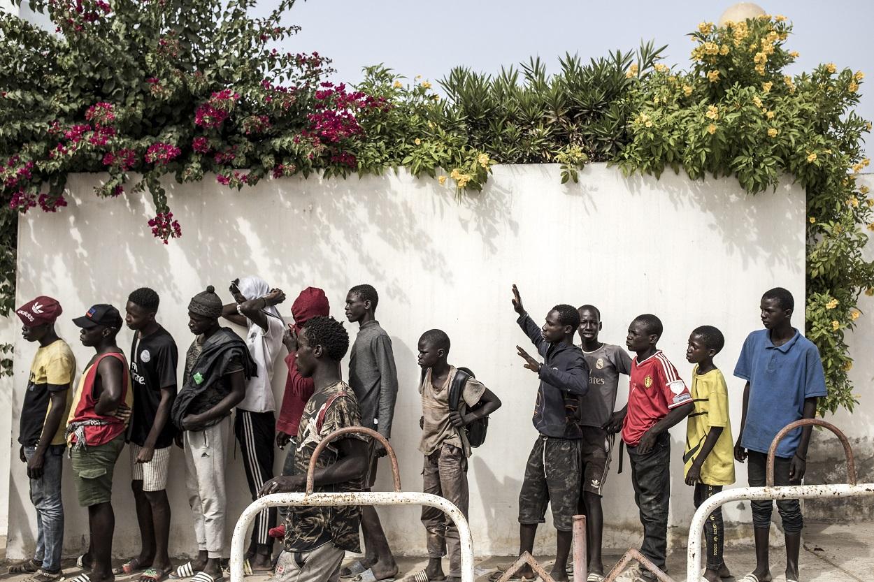 Chicos de la calle, llamados talibé, hacen cola para recibir ayuda y alimentos de una ONG, en Dakar, la capital de Senegal. AFP/JOHN WESSELS