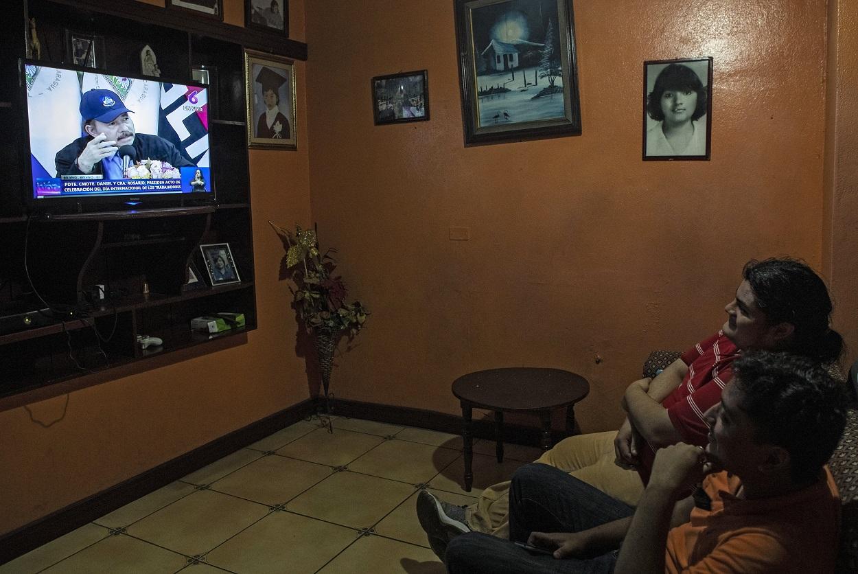 Dos hombres en su casa viendo por televisión la intervención del presidente de Nicaragua, Daniel Ortega, en Managua. AFP/INTI OCON
