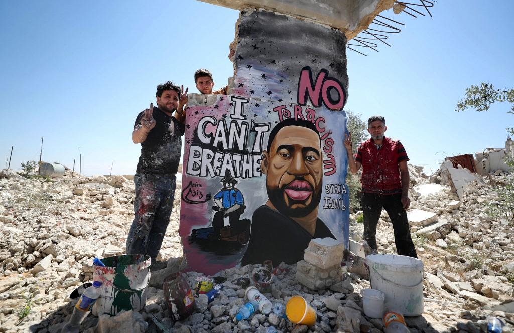 Los artistas sirios Aziz Asmar y Anis Hamdoun terminan un mural que representa a George Floyd, el afroamericano desarmado que murió mientras era arrestado por un oficial de policía de Minneapolis, en la ciudad de Binnish en la provincia de Idlib, en el noroeste de Siria.AFP/OMAR HAJ KADOUR