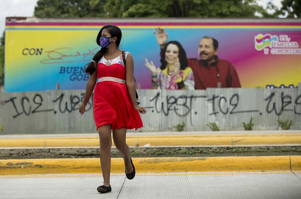 Una joven con mascarilla pasa frente a un cartel del presidente de Nicaragua Daniel Ortega y su esposa Rosario Murill, en Managua. EFE/Jorge Torres