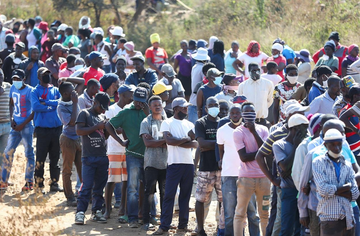 Multitud de personas haciendo cola para recibir ayuda alimentaria, en Sunderland Ridge (Sudáfrica), durante las restricciones impuestas por la pandemia del coronavirus. REUTERS / Siphiwe Sibeko