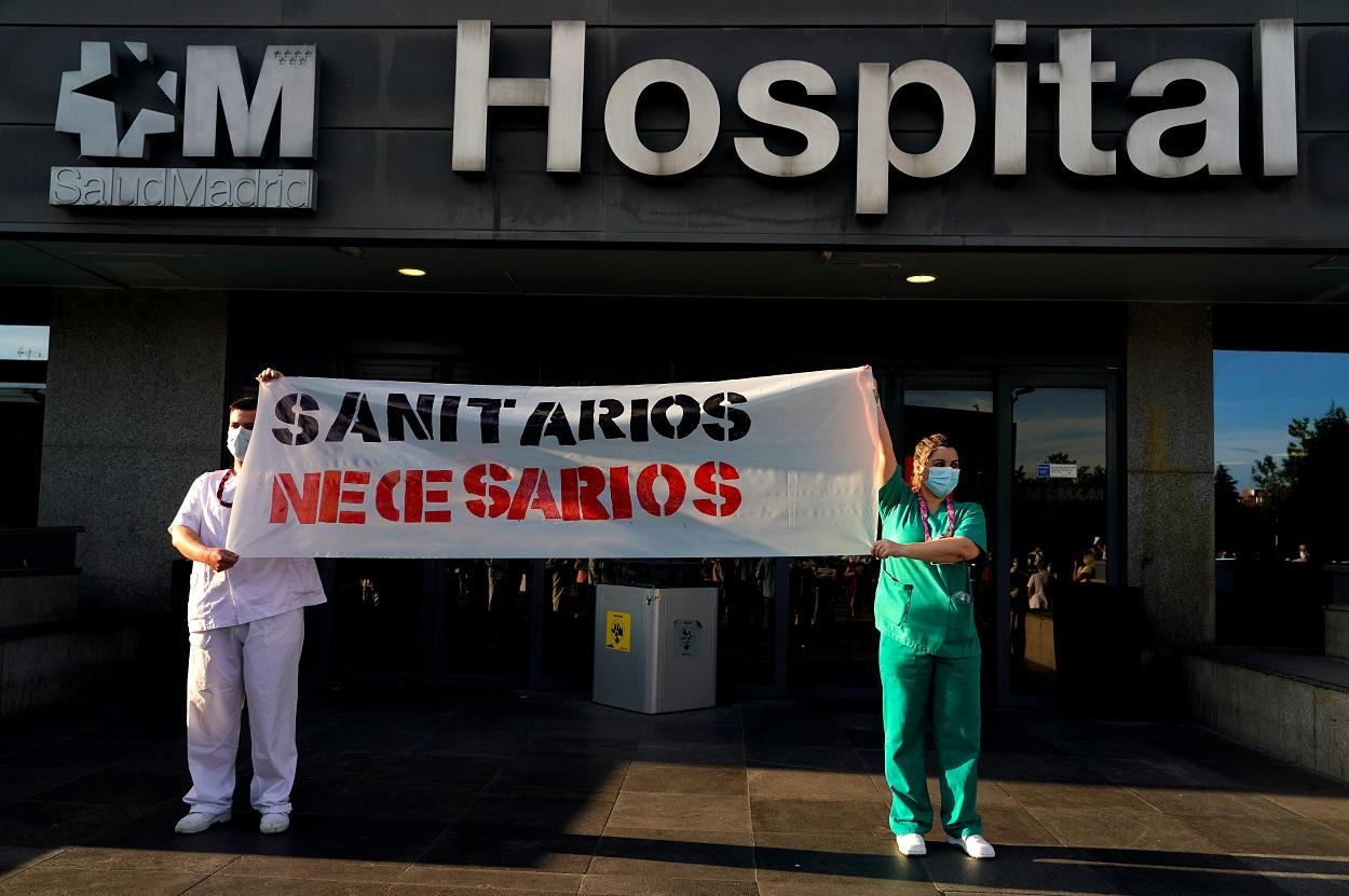 Dos trabajadores sanitarios del Hospital La Paz de Madrid sostienen una pancarta en la que reclaman más personal y medios. REUTERS/Juan Medina