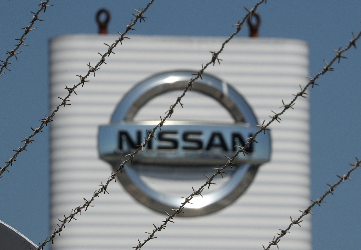 El logo de Nisan, a través de la alambrada que rodea su planta en la Zona Franca de Barcelona. REUTERS/ Albert Gea