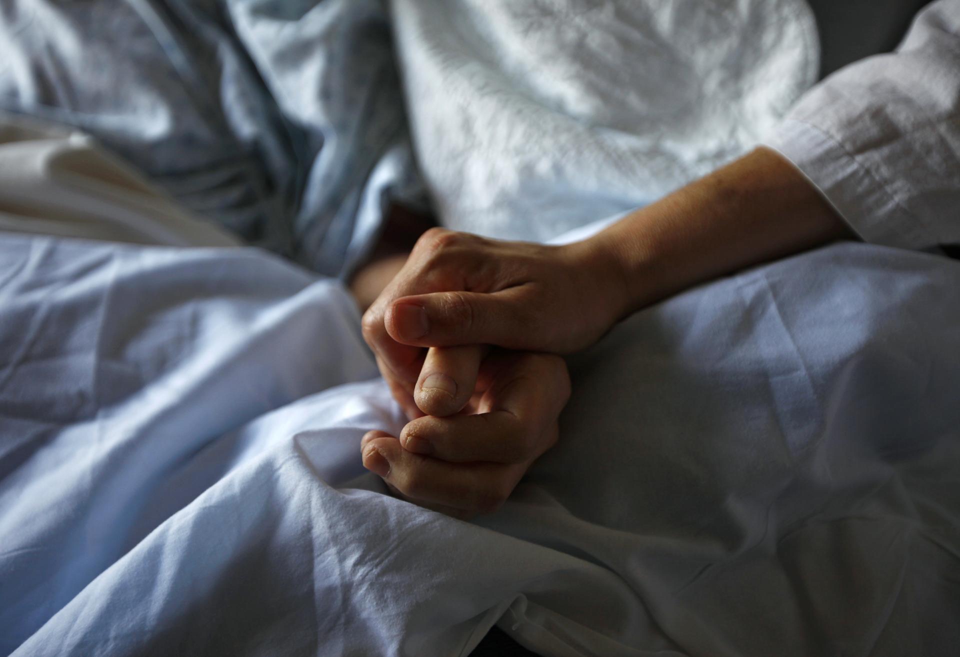 Una mujer sujeta la madre de su madre enferma de cáncer, en un hospital en EEUU. REUTERS