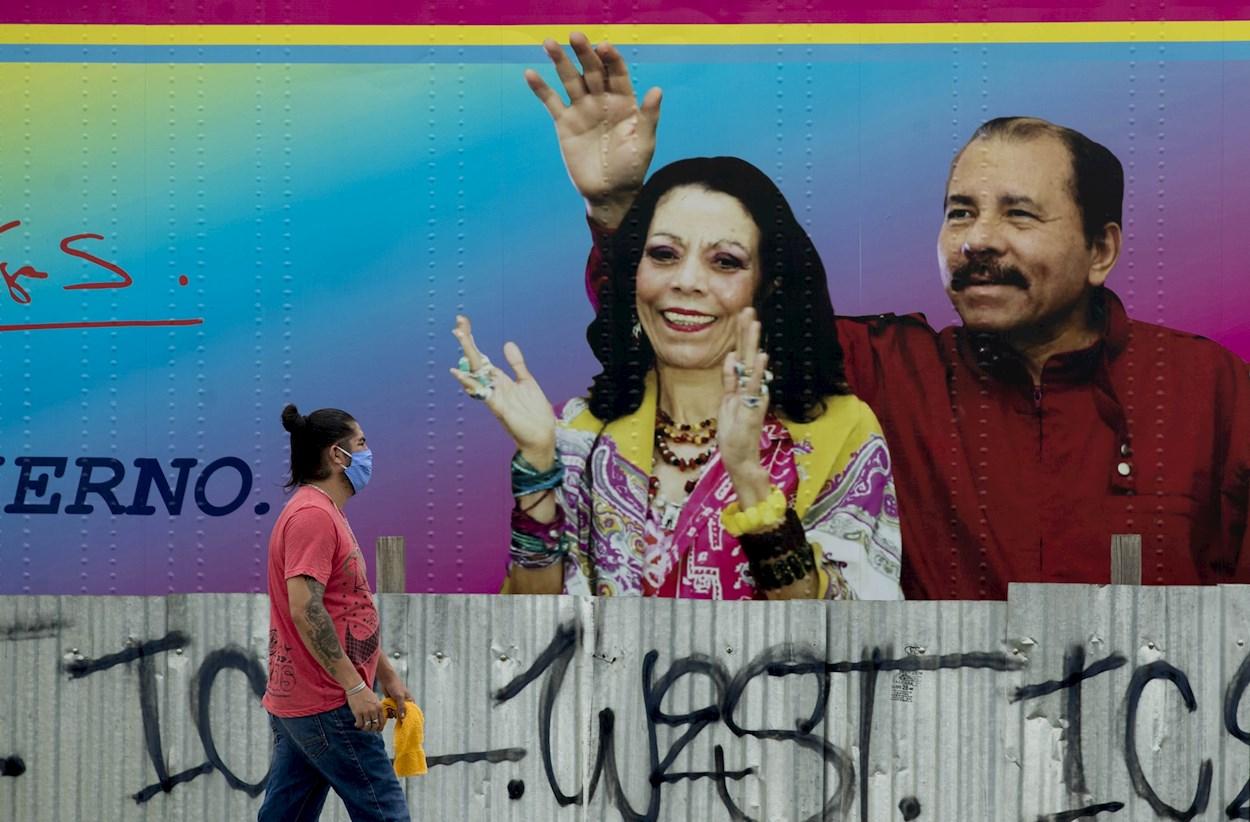Un hombre con mascarilla pasa delante de un cartel con la imagen del presidente de Nicaragua Daniel Ortega y su esposa Rosario Murillo, en Managua. EFE/Jorge Torres