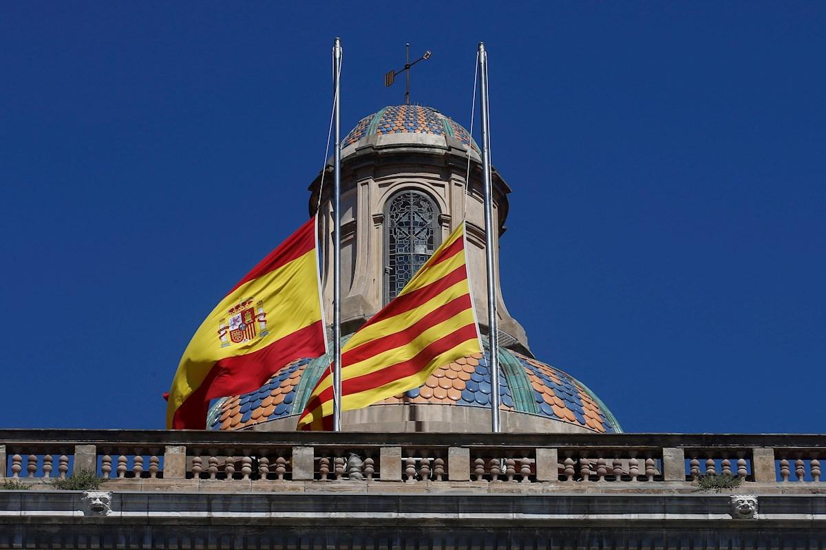 Las banderas de España y la senyera en el Palau de la Generalitat ondean en la posición de media asta durante el luto oficial por las víctimas de la covid-19. EFE/ Quique García