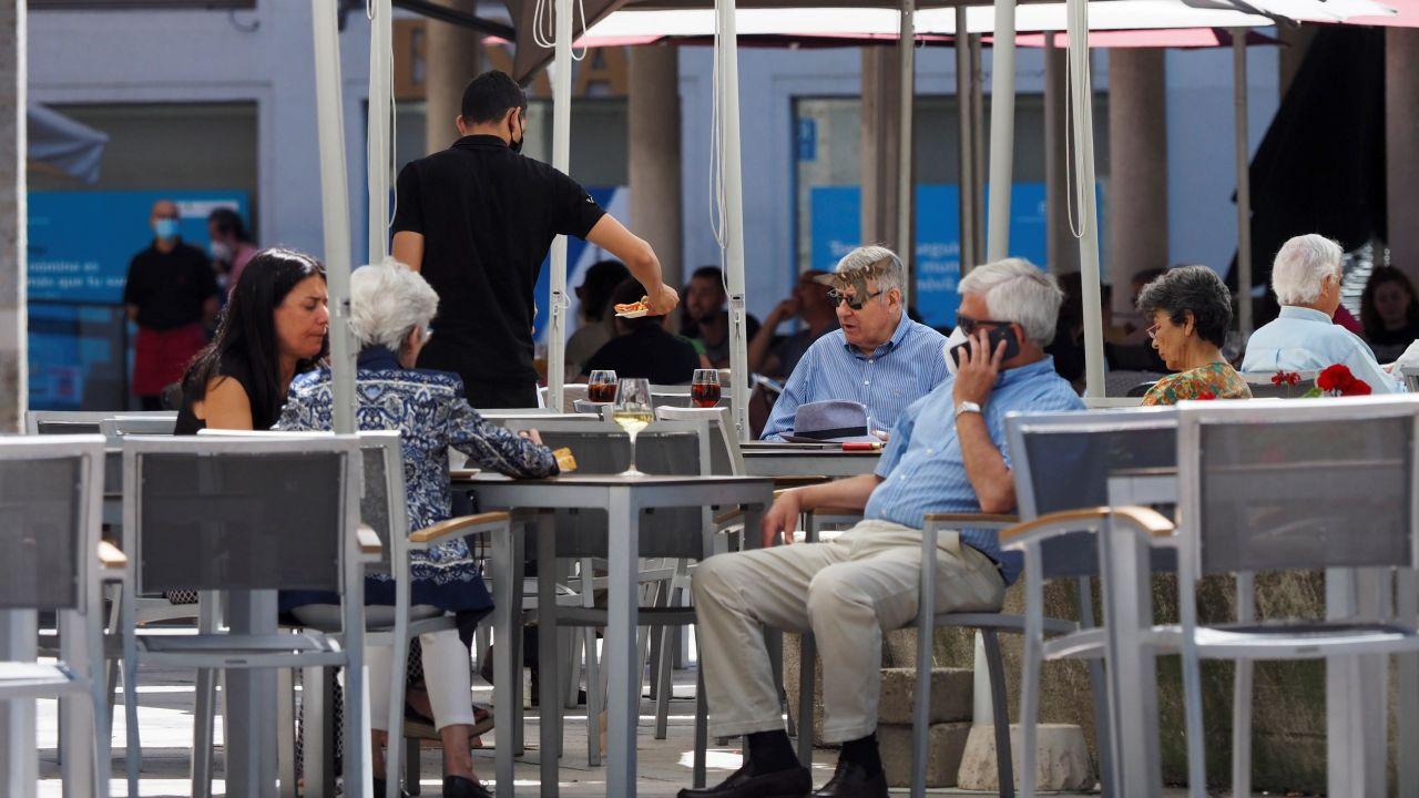 """Personas disfrutan de un soleado día en la terraza de un restaurante en la plaza de la Rinconada, este domingo en Valladolid. Después de 98 días de estado de alarma, Castilla y León entra en una """"nueva normalidad"""" regida por unas medias que, aunque más relajadas que las anteriores, tratarán de preservar la prevención y el control de la Covid-19. EFE/R.García"""