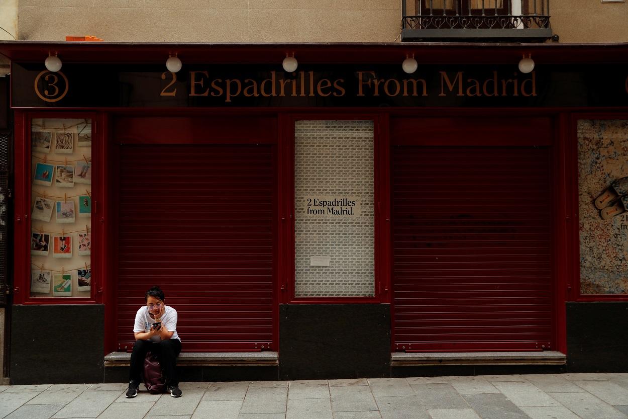 Una joven mira su móvil, sentada en la puerta de una tienda cerrada en el centro de Madrid. REUTERS/Susana Vera