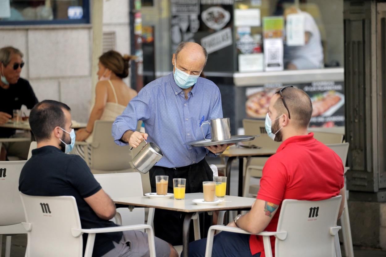 Un camarero sirve a dos clientes en una terraza de un bar en Madrid. REUTERS/Javier Barbancho
