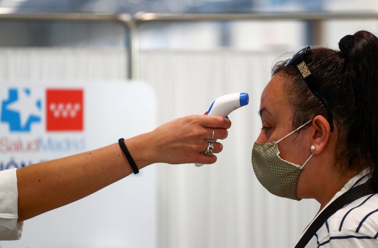 Una sanitaria toma la tempreatura a una mujer en un centro de atención primaria de la Comunidad de Madrid. REUTERS/Sergio Perez