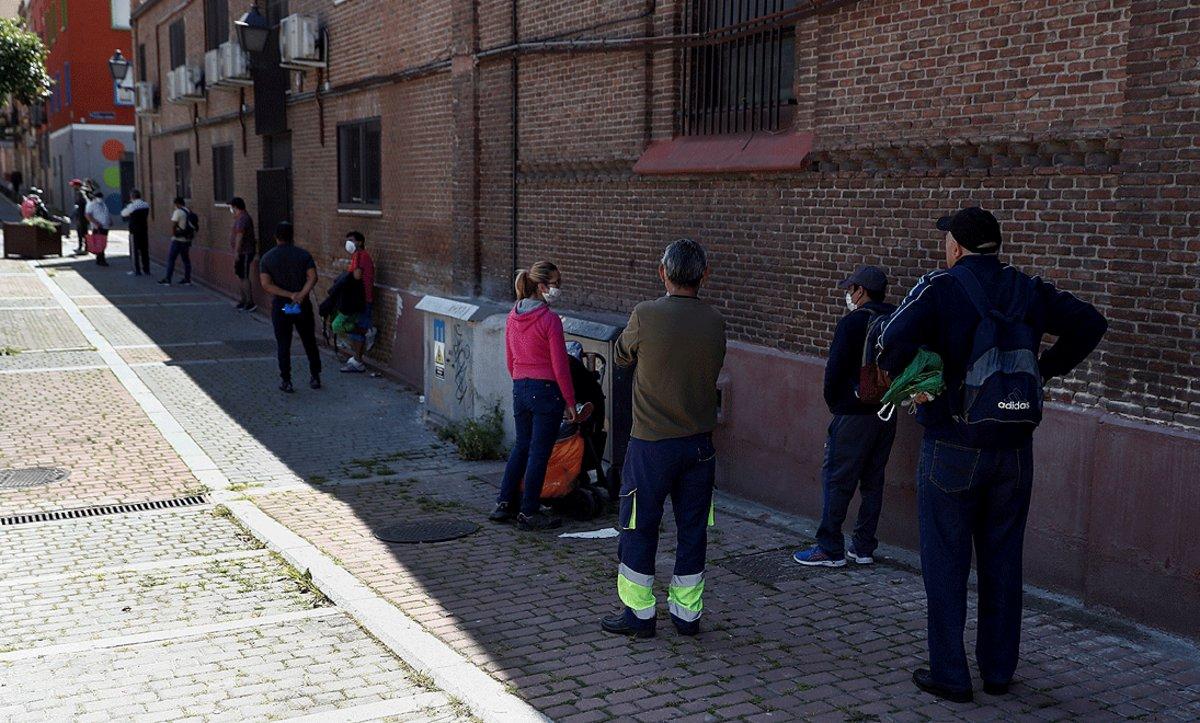 Cola para recoger alimentos en un comedor social de una parroquia, en Puente de Vallecas (Madrid). EFE