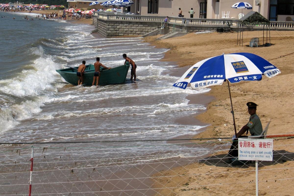 Un agente vigila la zona de la playa de la localidad costera china de Beidaihe reservada para los funcionarios del Gobierno. REUTERS