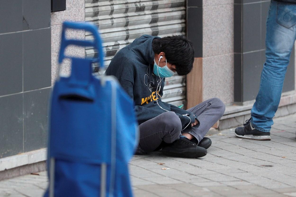 Una persona espera sentada en el suelo en una fila para recoger alimentos. EFE/Rodrigo Jiménez