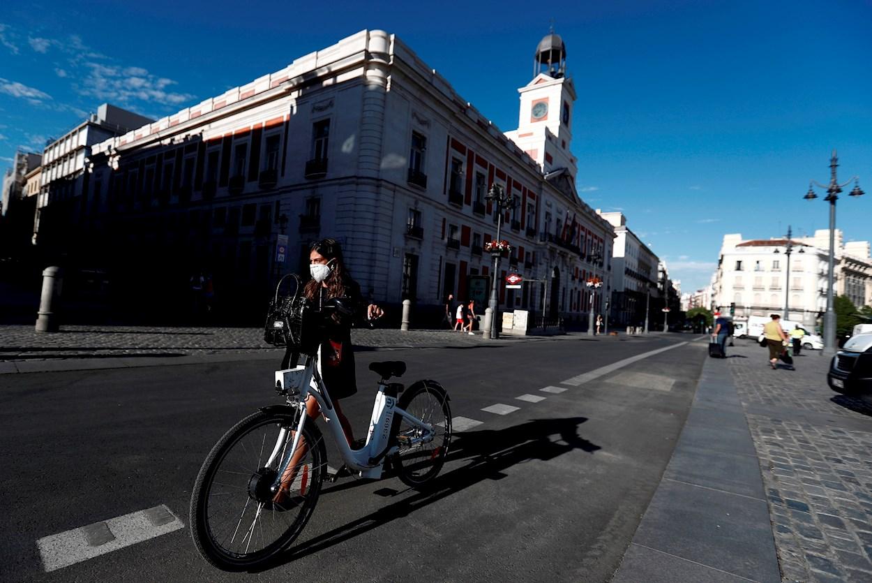 Una ciclista cruza la Puerta del Sol, en Madrid. EFE/Mariscal