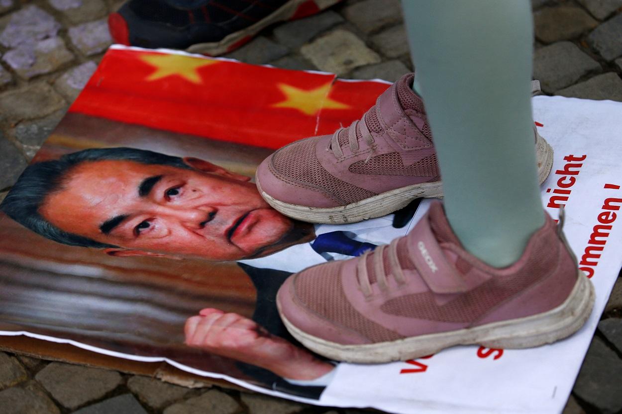 Un manifestante pisa un retrato del ministro de Exteriores chino, Wang Yi, en una manifestación a favor de Hong Kong, durante la visita del canciller a Alemania. REUTERS/Michele Tantussi