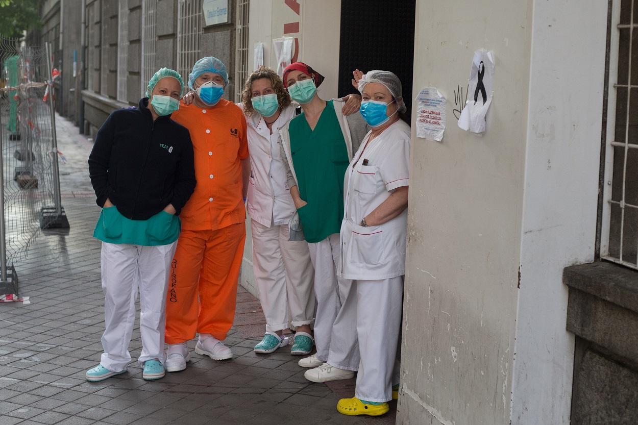 Un grupo de sanitarios posa para la foto junto a un lazo de luto por los fallecidos por coronavirus en el Hospital de la Princesa durante la pandemia de Covid-19. E.P./Joaquin Corchero