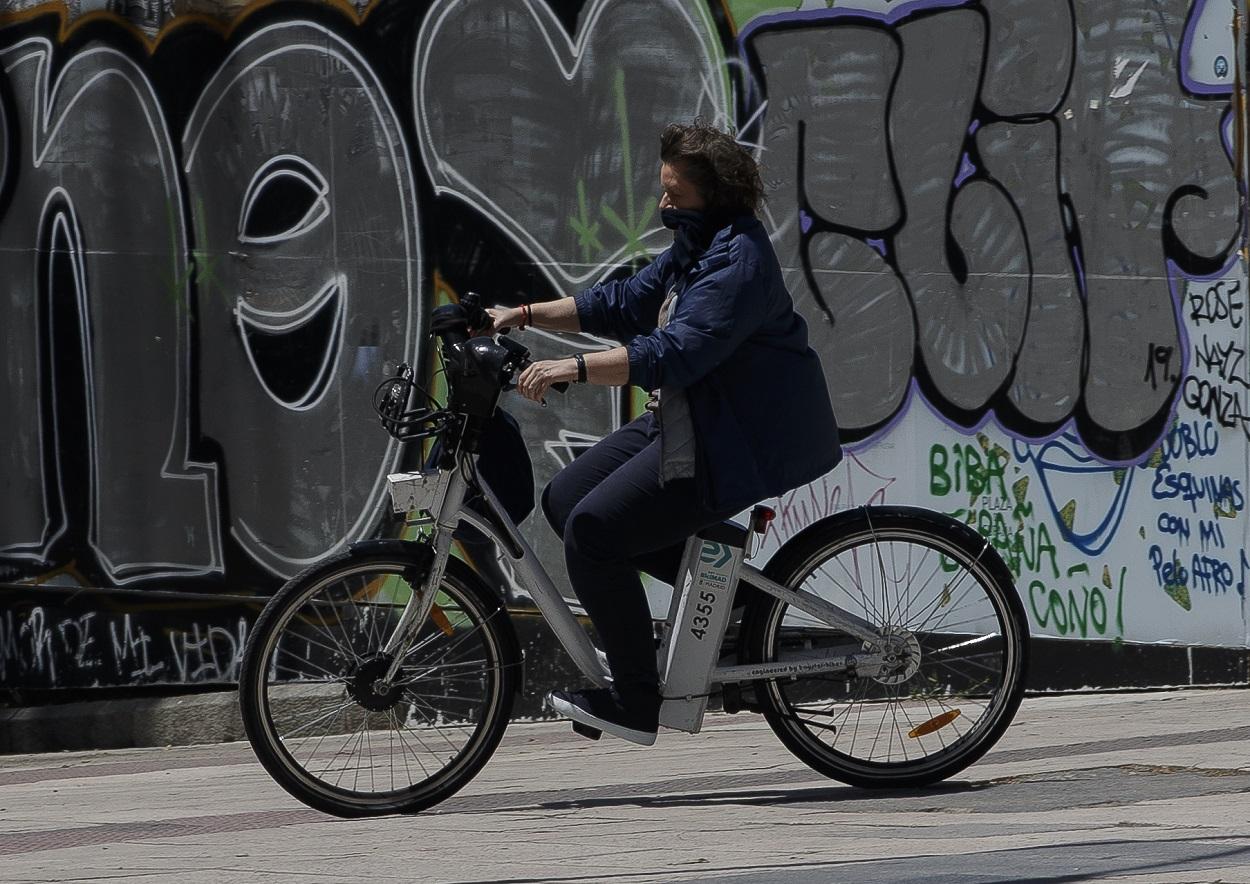 Una mujer protegida con mascarilla monta en una bicicleta de BiciMAD. E.P./Eduardo Parra