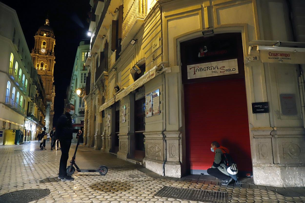 Un camarero cierra el bar ubicado en el centro de Málaga, como consecuencia del toque de queda impuesto por el Gobierno para poder frenar el coronavirus. E.P./Álex Zea