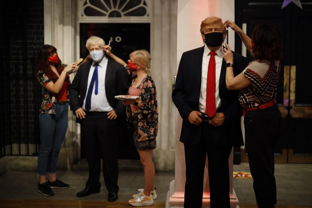 Operarias del Museo Madame Tussauds, de Londres, dan los últimos retoques a las figuras de cera que representan a Boris Jonhnson y a Donald Trump, antes de su reapertura el pasado verano, tras el cierre por la pandemia del coronavirus. AFP/Tolga Akmen