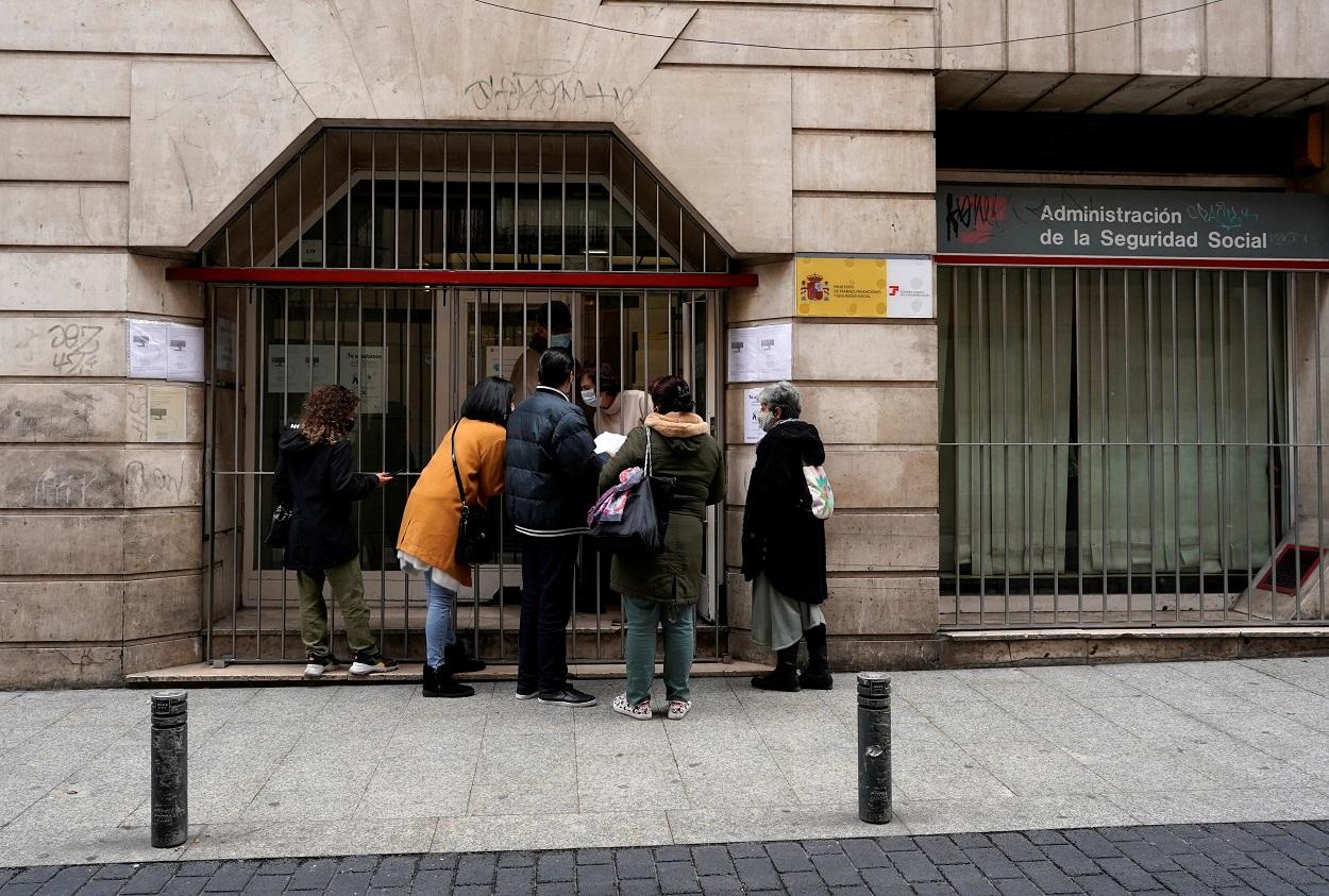 Varias personas son atendidas por un funcionario en la puerta de unas oficinas del Ministerio de Trabajo, en Madrid. REUTERS/Juan Medina