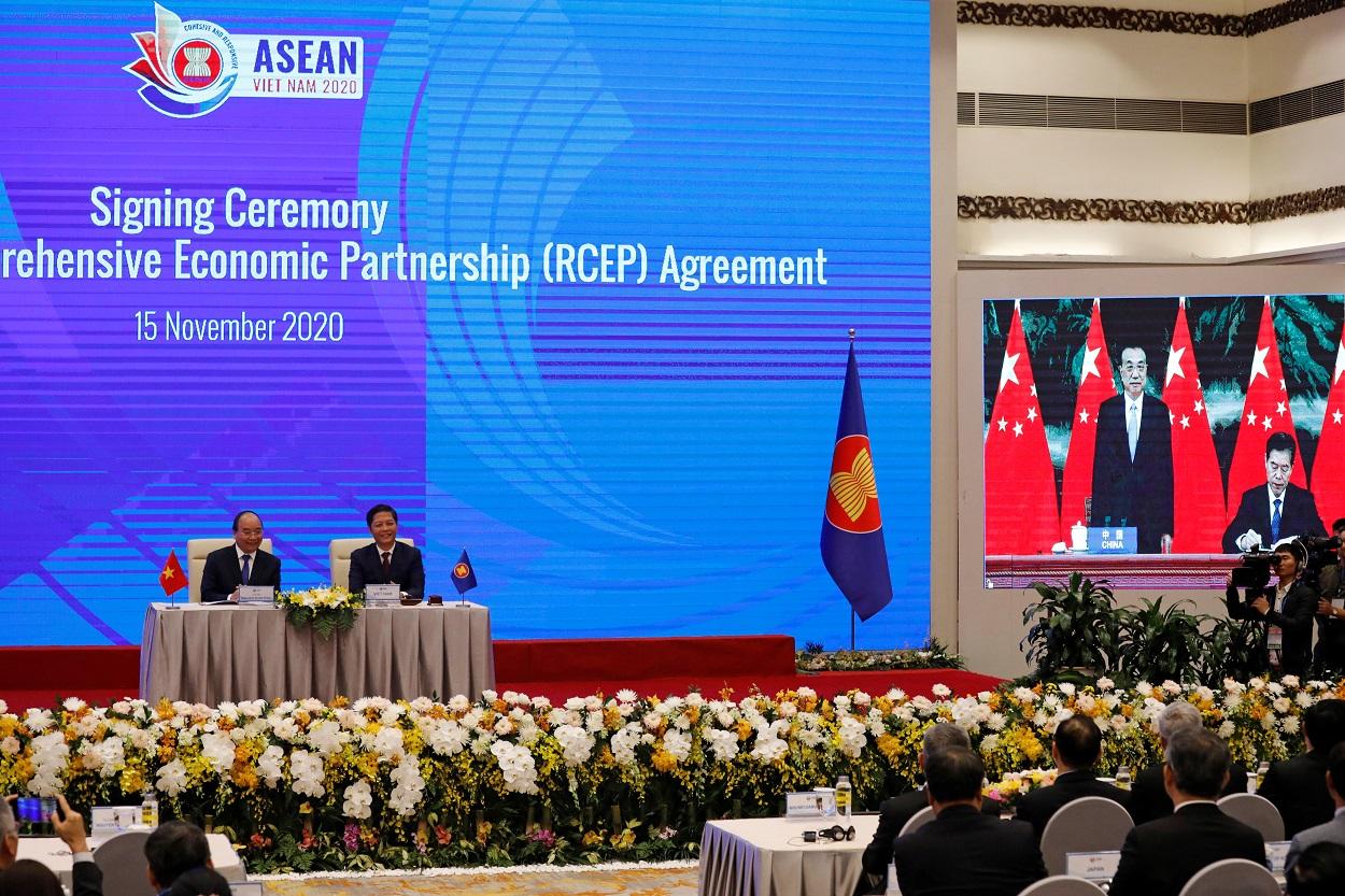 El primer ministro de Vietnam, Nguyen Xuan Phuc (izq.), con el ministro de Industria y Comercio, Tran Tuan Anh, mientras ven una pantalla que muestra al ministro de Comercio chino, Zhong Shan firmando junto al primer ministro chino Li Keqiang, el acuerdo para la Asociación Económica Integral Regional (RCEP, según sus siglas en inglés) durante la 37 Cumbre de la ASEAN, en Hanoi (Vietnam). REUTERS/Kham