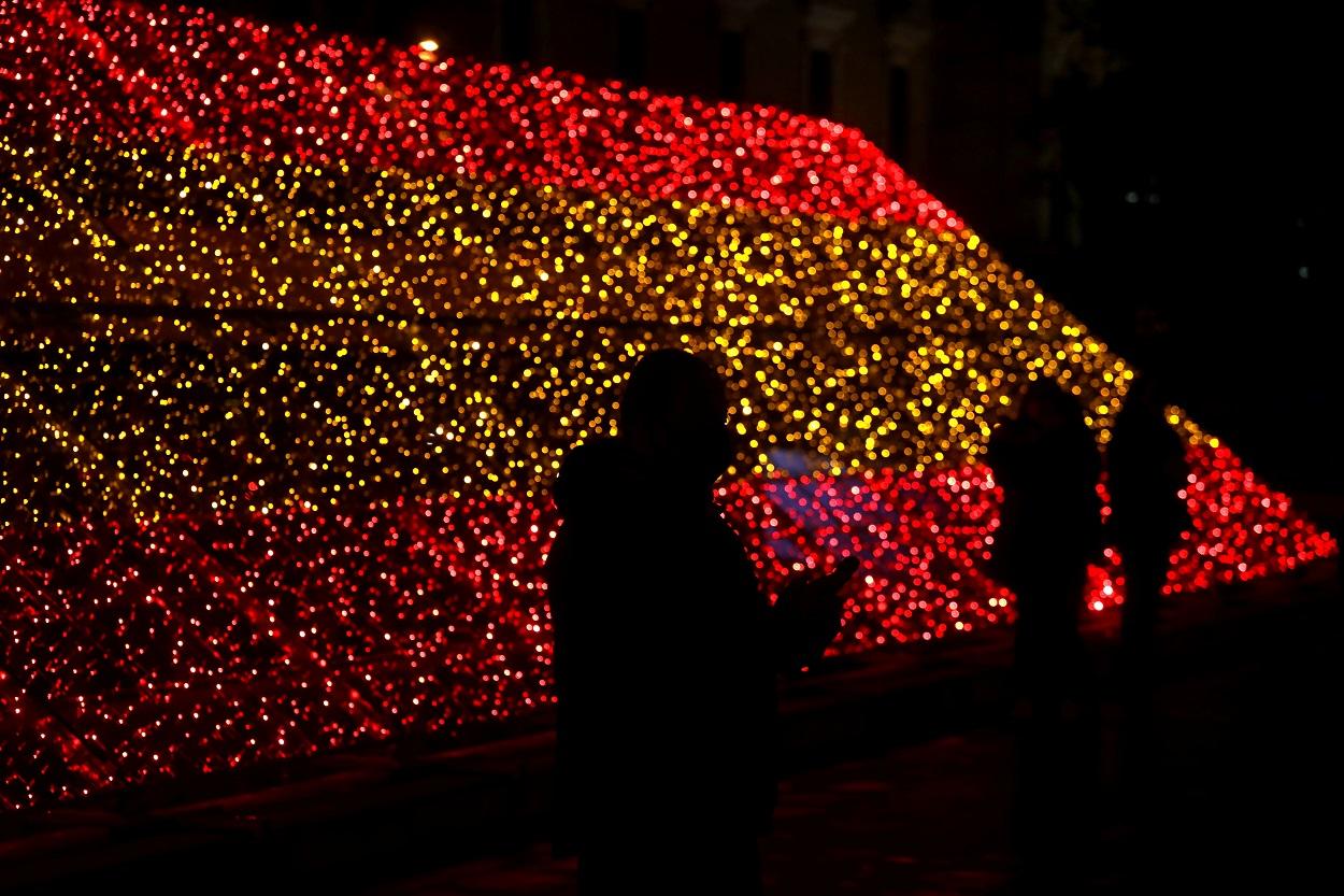 Varias personas pasan junto a la iluminación navideña colocada por el Ayuntamiento de Madrid con los colores de la bandera de España. REUTERS/Sergio Perez