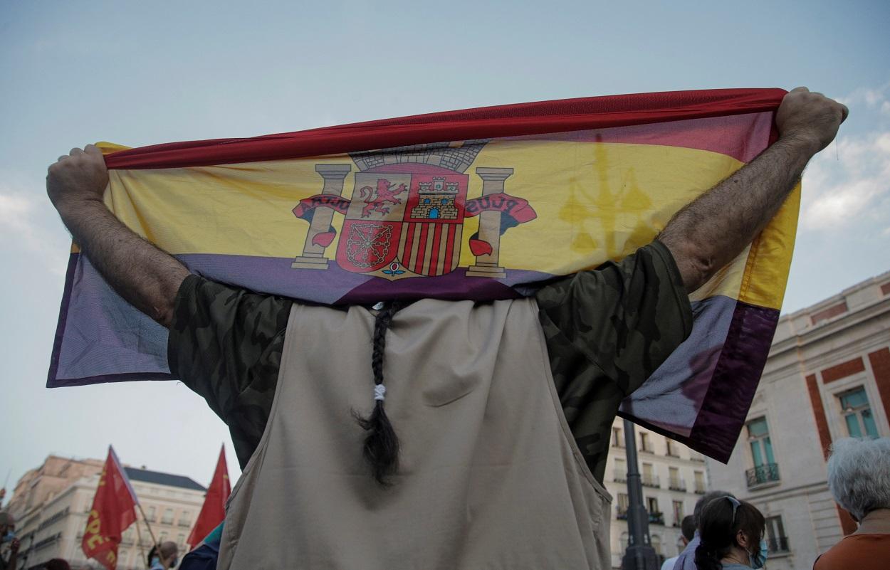 Una persona sostiene una bandera republicana durante las protestas contra la monarquía, tras la salida de España del rey emérito Juan Carlos I, por el escándalo sobre sus cuentas. REUTERS/Javier Barbancho