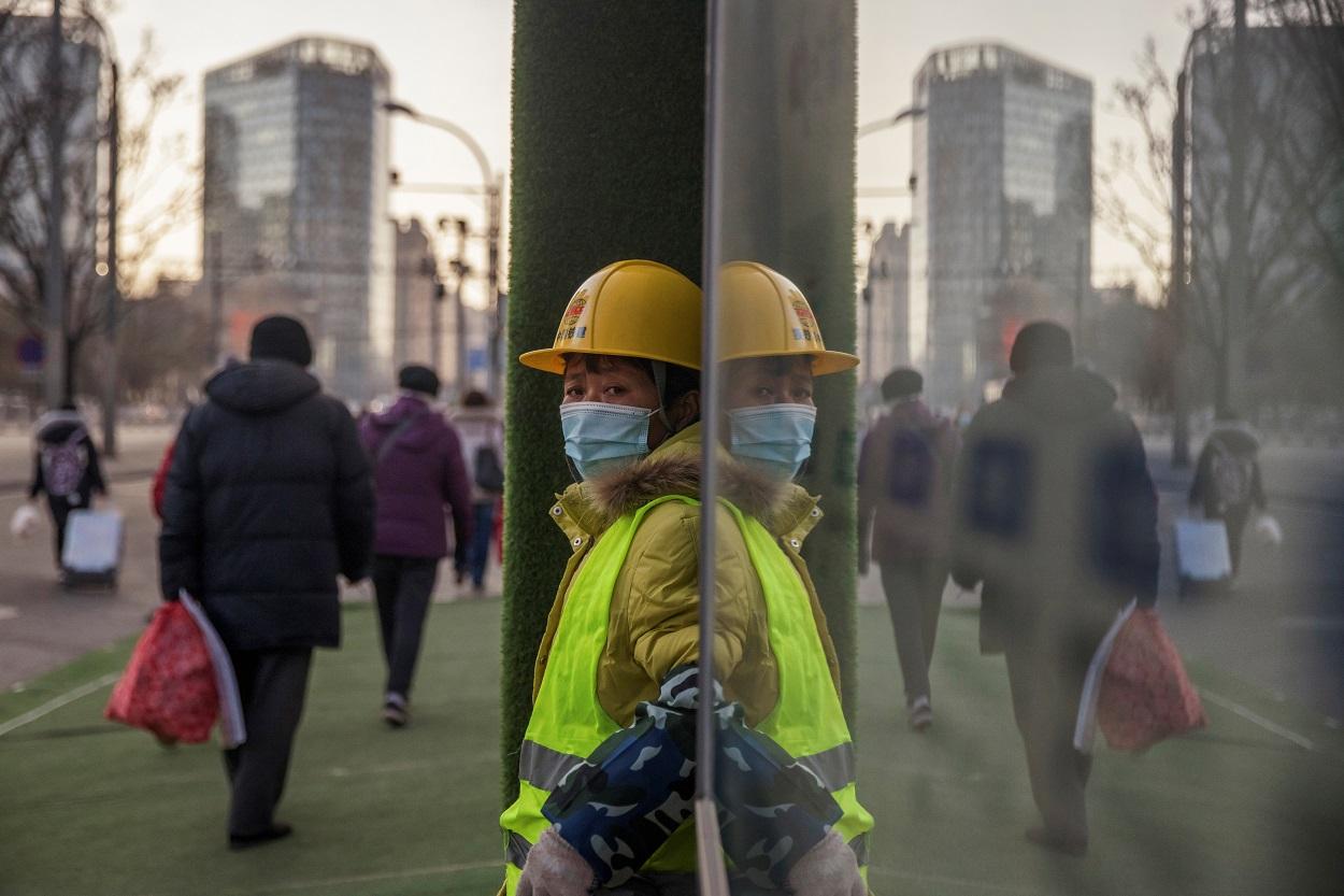 Un trabajador con mascarilla, en el exterior de un edificio en construcción en Pekín (China). REUTERS/Thomas Peter