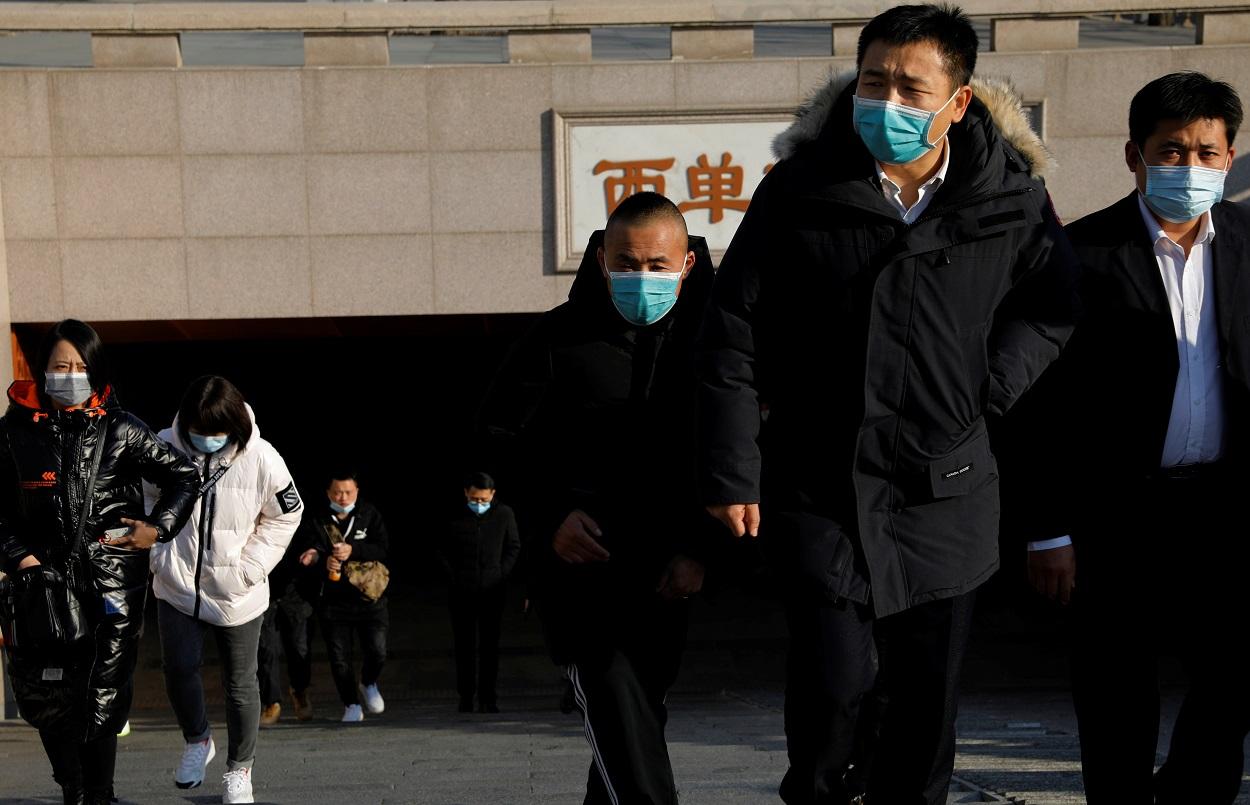 Varias personas con mascarilla salen de una boca de metro en Pekín. REUTERS/Tingshu Wang