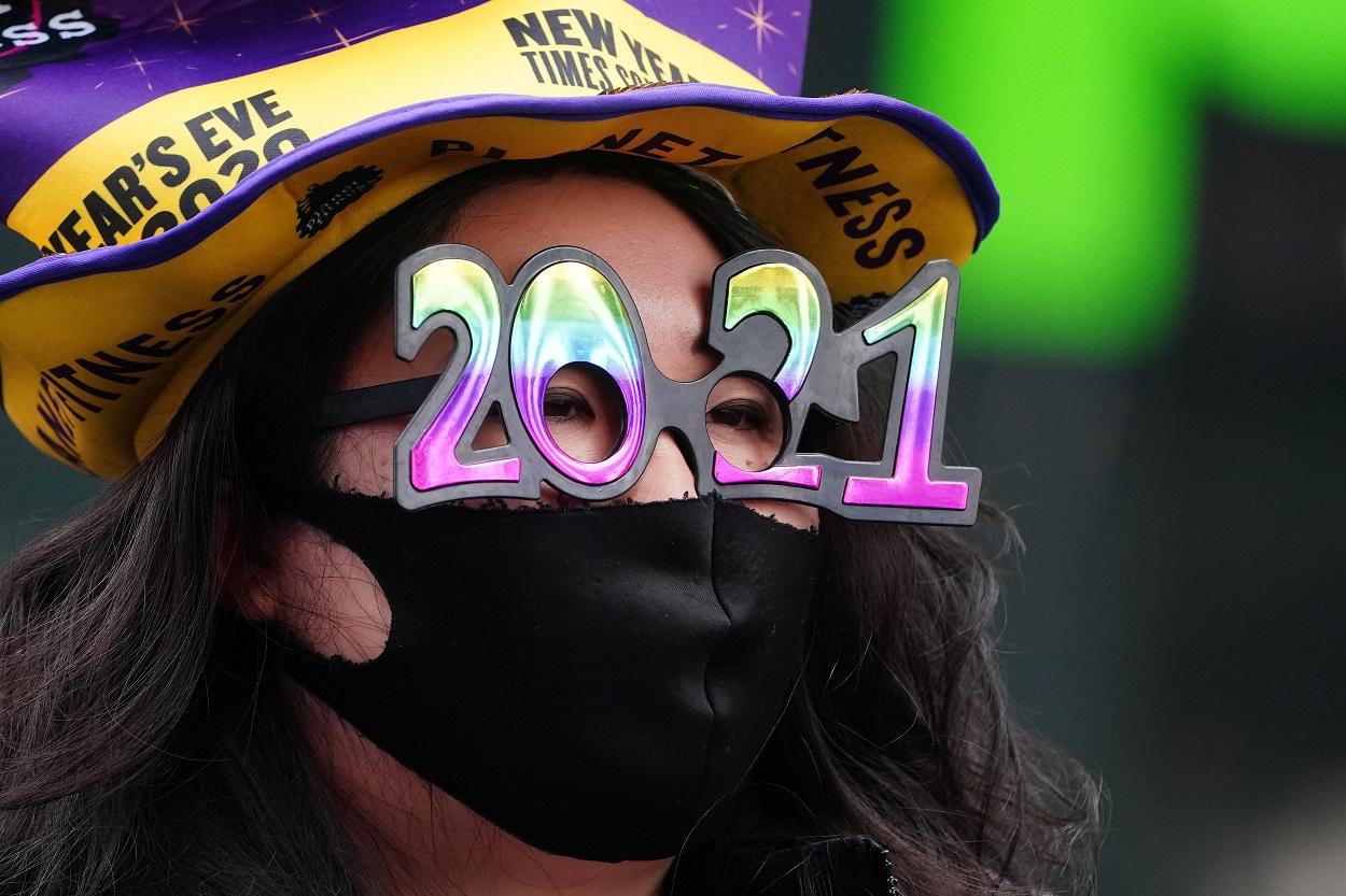 Una mujer con unas gafas con la forma del número 2021, en Times Square (Nueva York, EEUU). REUTERS/Carlo Allegri