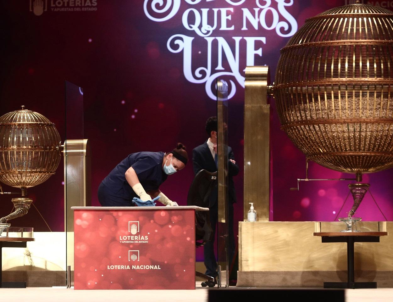 Una empleada limpia la mesa del sorteo de Lotería de Navidad para que se cumplan todas las medidas de higiene. E.P./Eduardo Parra