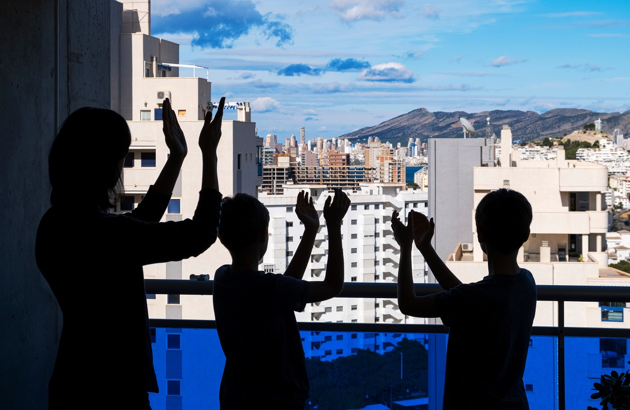 Una familia aplaude a los sanitarios durante el confinamiento de la primavera de 2020. Shutterstock / Veja