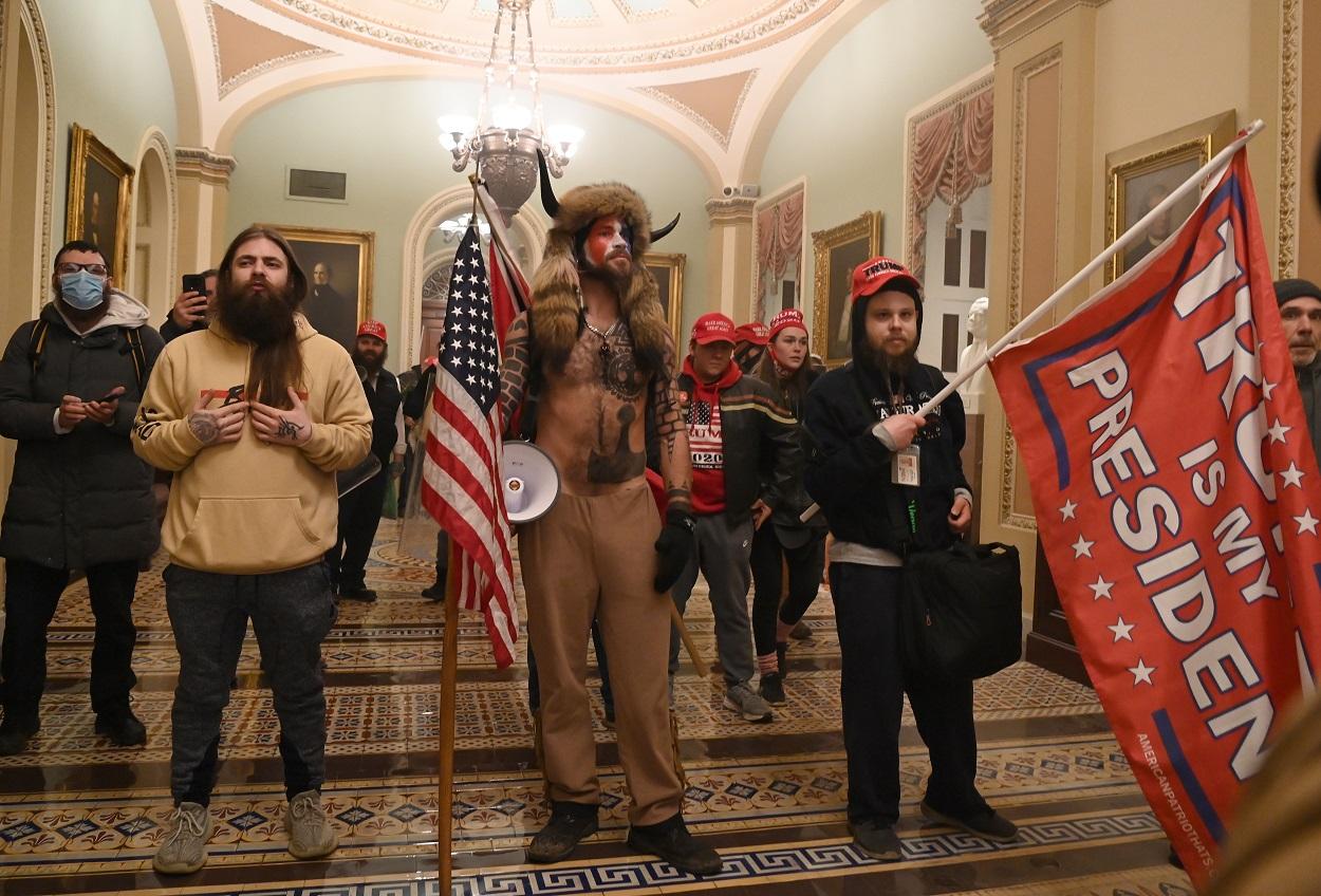 En el centro de la imagen, vestido con pieles, Jake Angeli, miembro del movimiento de teorías de la conspiración Qanon, y que se hace llamar 'Yellowstone Wolf', con otros seguidores de Donald Trump, en su asalto al Capitolio de EEUU, en Washington. AFP/Saul LOEB