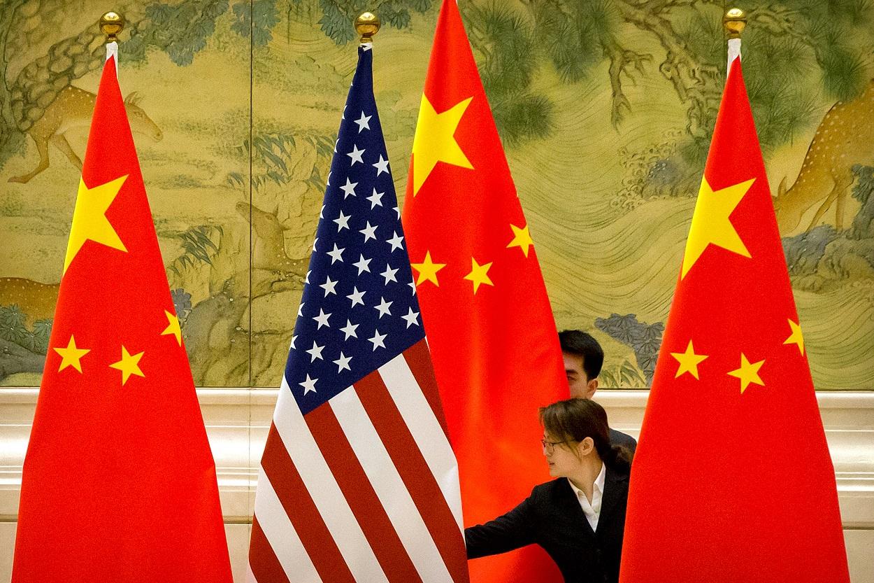 La bandera de Estados Unidos entre varias de China, antes de una sesión de las negociaciones comerciales entre ambos países, en Pekín, en febrero de 2019. REUTERS/Mark Schiefelbein / Pool