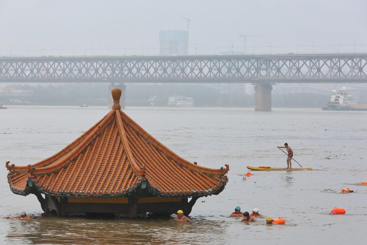 Varias personas nadan cerca de un pabellón parcialmente sumergido en las aguas del río Yangtze, tras las fuertes lluvias en Wuhan, provincia de Hubei (China). REUTERS