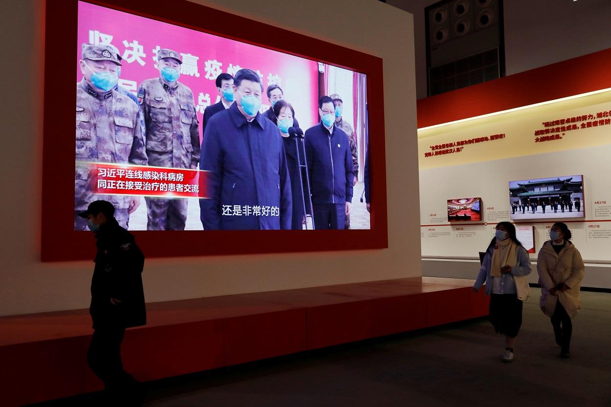 Los visitantes caminan cerca de una pantalla que muestra al presidente chino, Xi Jinping, durante una exposición sobre la lucha contra el coronavirus (COVID-19), en el Centro de Convenciones de Wuhan. REUTERS / Tingshu Wang