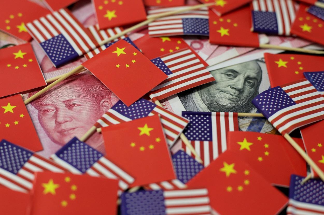 Billetes de dólar y de yuan, entre banderas de EEUU y de China.. REUTERS/Jason Lee/Illustration