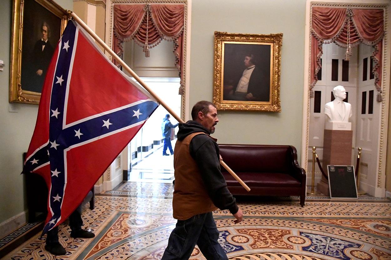 Un seguidor de Donald Trump con la bandera confederada, por las dependencias del Senado, en el edificio del Capitolio de EEUU, en Washington. REUTERS/Mike Theiler