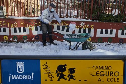 Familias colaboran en la limpieza del hielo del Colegio Amadeo Vives (Madrid)