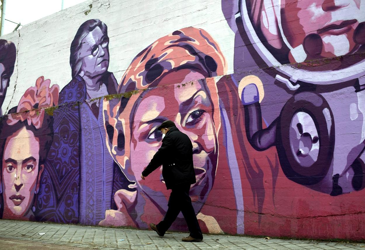Un hombre pasa por el mural feminista en el polideportivo municipal de la Concepción en el distrito de Ciudad Lineal, en Madrid. E.P./Óscar Cañas
