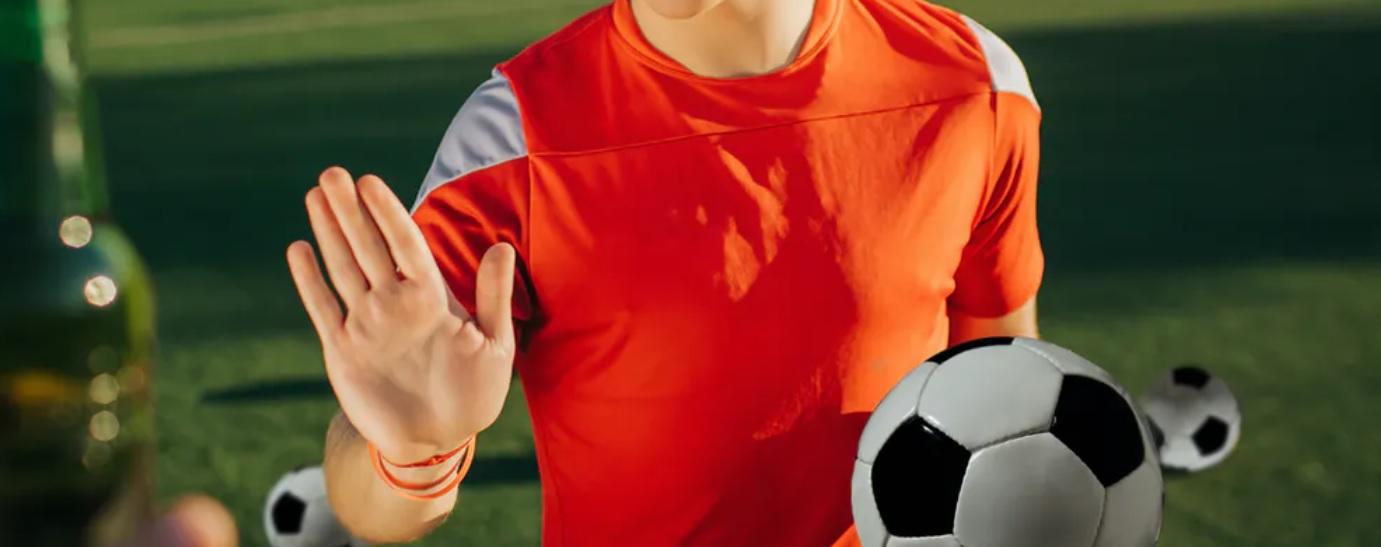Chico con equipación de fútbol sosteniendo un balón