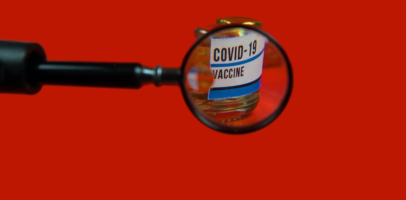 Dosis de vacuna contra la covid-19 observada a través de una lupa.