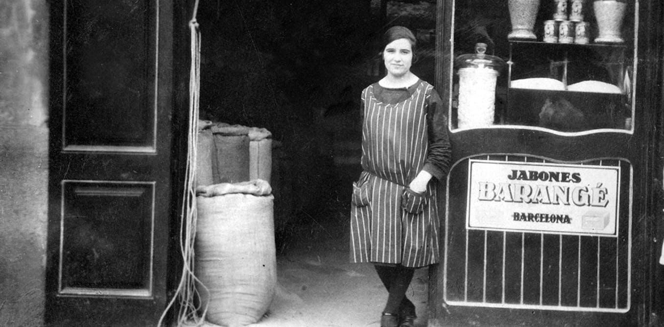 Retrato antiguo de una mujer ante la entrada de la droguería de la Rambla de la Libertad, en Girona.