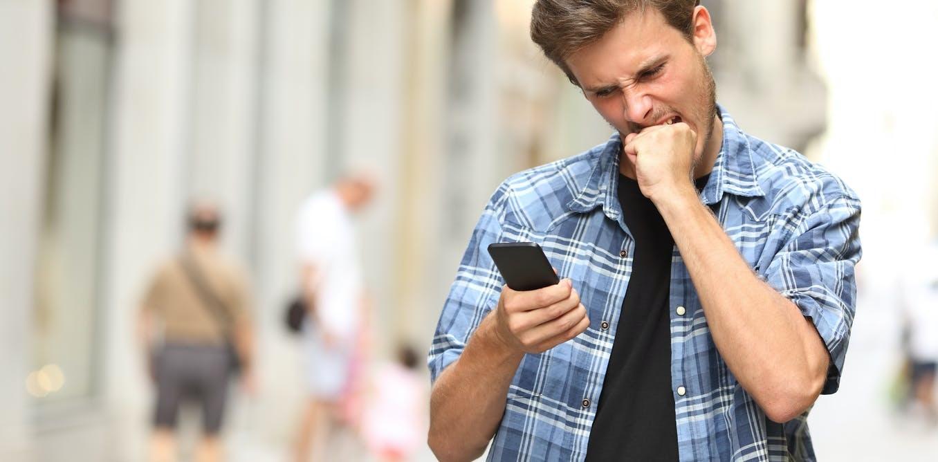 Un hombre, que se encuentra mirando un teléfono móvil, muestra una mueca molesta.