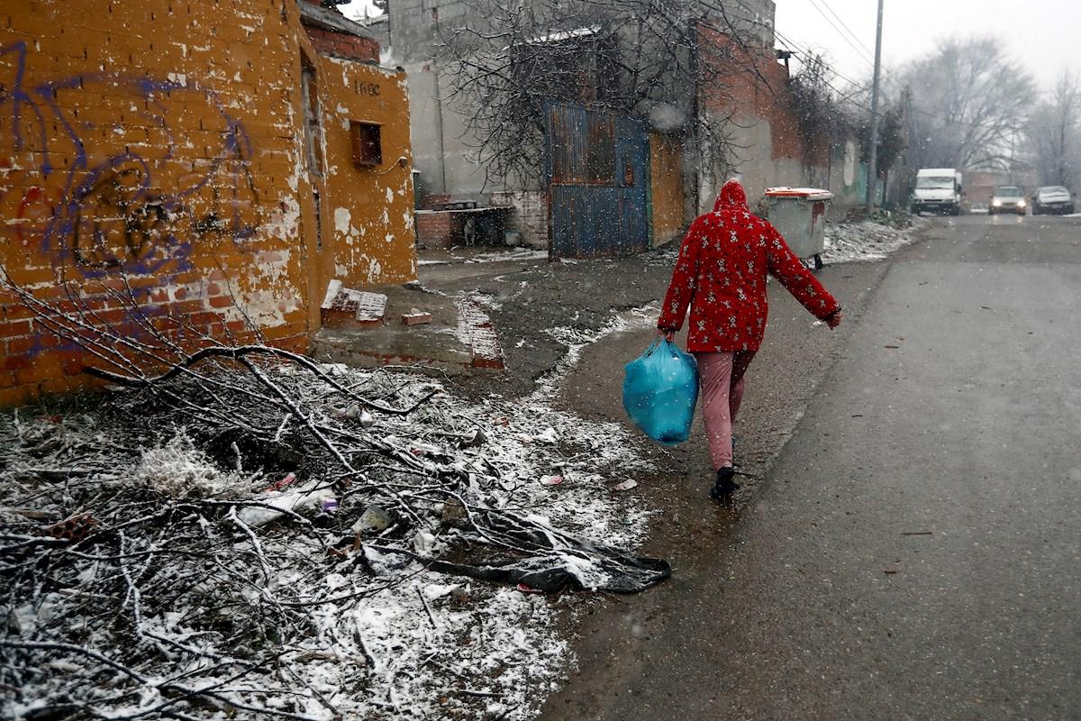 Una vecina del asentamiento de la Cañada Real camina bajo la nieve. EFE/Mariscal