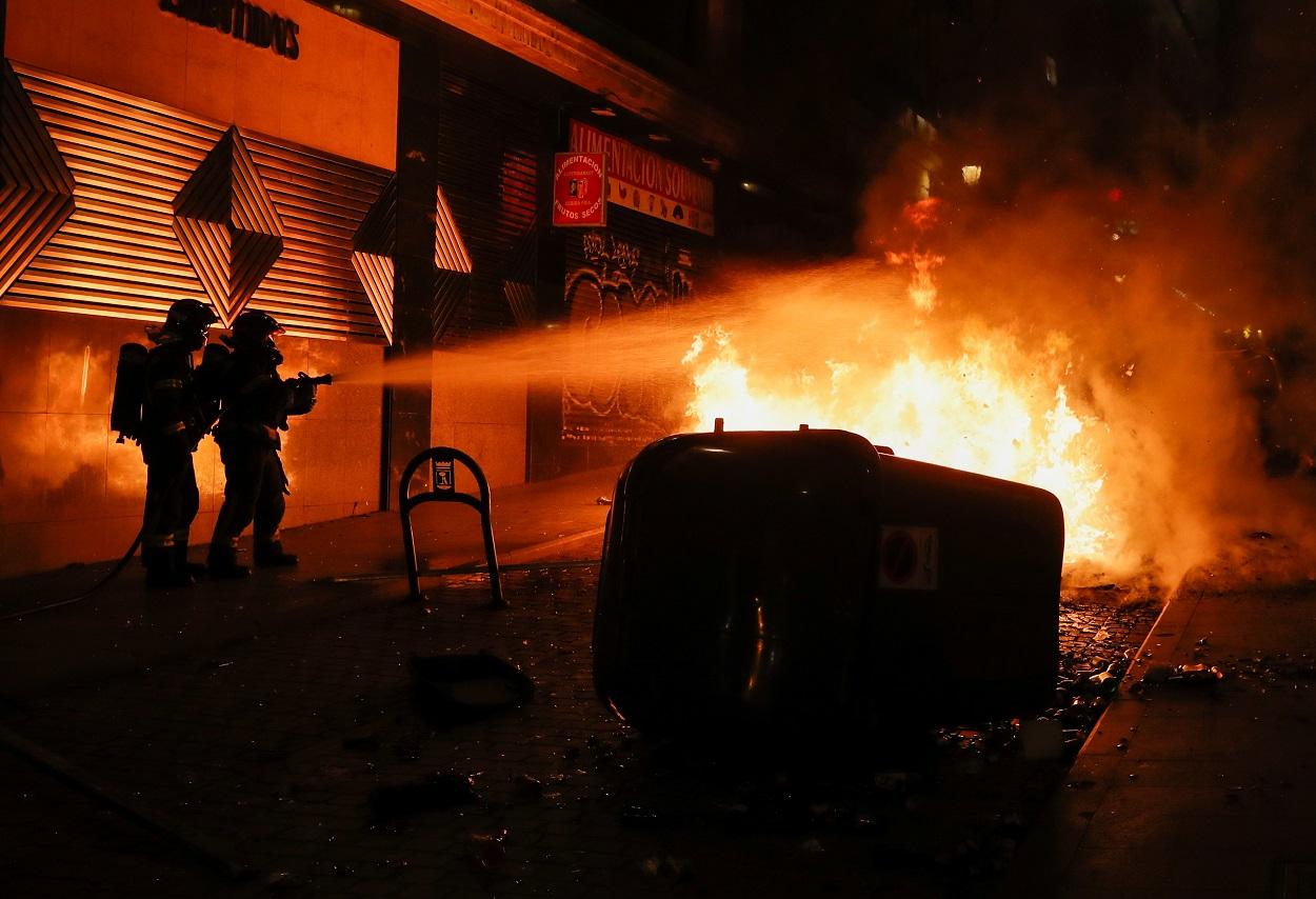 Los bomberos tratan de apagar las llamas en un contenedor incendiado durante las manifestaciones en Madrid en protesta por la entrada en prisión del rapero Hasél.. REUTERS/Susana Vera